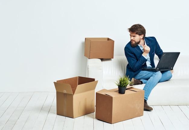 Geschäftsmann, der auf der couch sitzt und büroleiter-profis bewegt