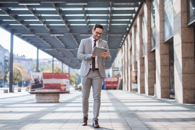 Geschäftsmann, der auf der straße geht und tablette benutzt, um eine e-mail zu überprüfen. im hintergrund business center exteriour.