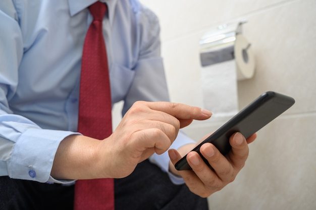Geschäftsmann, der auf der toilette im badezimmer sitzt und ein smartphone benutzt.