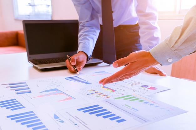 Geschäftsmann, der auf diagramm und diagramm im büro zeigt.