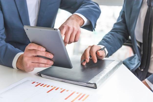 Geschäftsmann, der auf digitaler tablette am arbeitsplatz sich bespricht