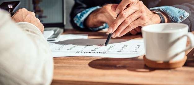 Geschäftsmann, der auf ein bestimmtes datum an einem kalender zeigt