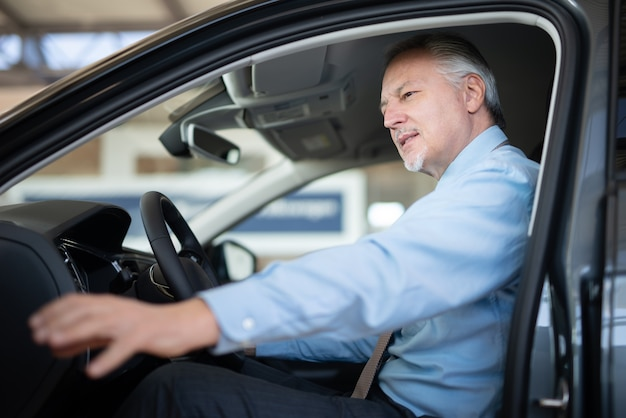 Geschäftsmann, der auf einem auto an einem autohändler-salon sitzt