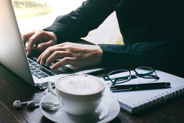 Geschäftsmann, der auf einem laptop beim trinken des kaffees in einem café schreibt