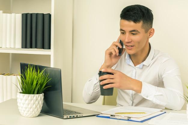 Geschäftsmann, der auf einem mobiltelefon spricht und an seinem laptop im büro arbeitet