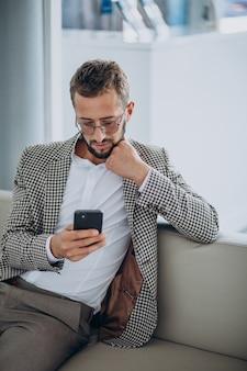 Geschäftsmann, der auf einem sofa sitzt und telefon benutzt