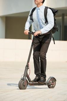 Geschäftsmann, der auf elektroroller reitet