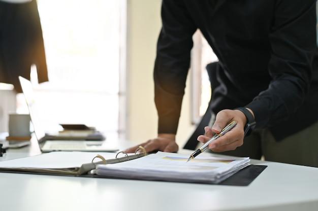 Geschäftsmann, der auf finanzdiagramm und -diagramm auf analysedokumentgebrauch zeigt, damit pläne qualität verbessern.