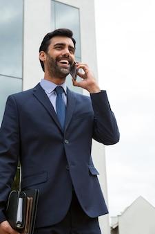 Geschäftsmann, der auf handy nahe bürogebäude spricht