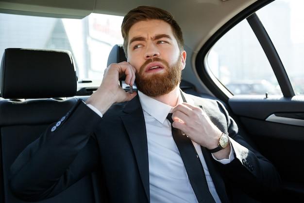 Geschäftsmann, der auf handy spricht und seine krawatte berührt