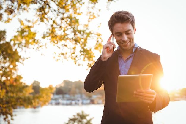 Geschäftsmann, der auf handy spricht, während digitales tablett verwendet wird