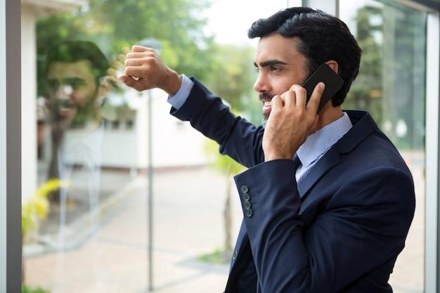 Geschäftsmann, der auf handy spricht, während er durch das fenster im konferenzzentrum schaut