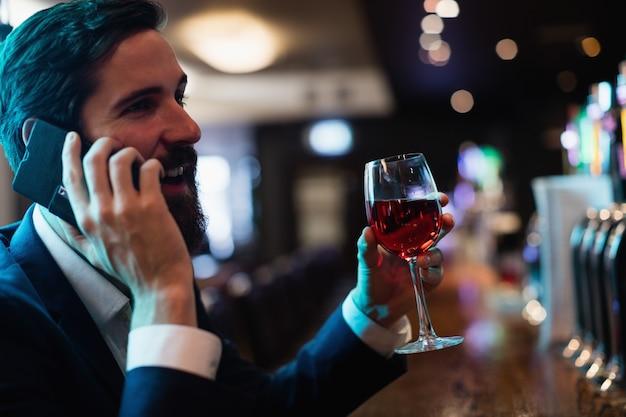 Geschäftsmann, der auf handy spricht, während er ein glas wein hat