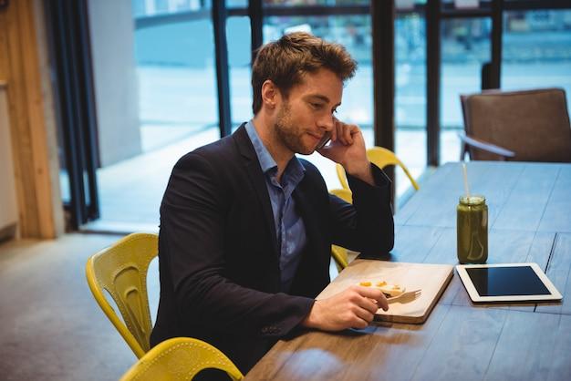 Geschäftsmann, der auf handy spricht, während er snacks hat