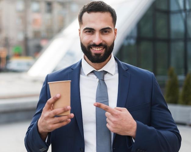 Geschäftsmann, der auf kaffee zeigt