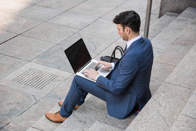 Geschäftsmann, der auf laptop auf straße schreibt