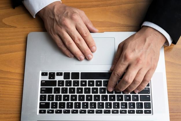 Geschäftsmann, der auf laptop schreibt
