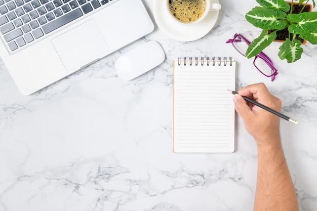 Geschäftsmann, der auf leerem notizbuch mit laptop und kaffee auf marmortisch schreibt. arbeitsplatzkonzept
