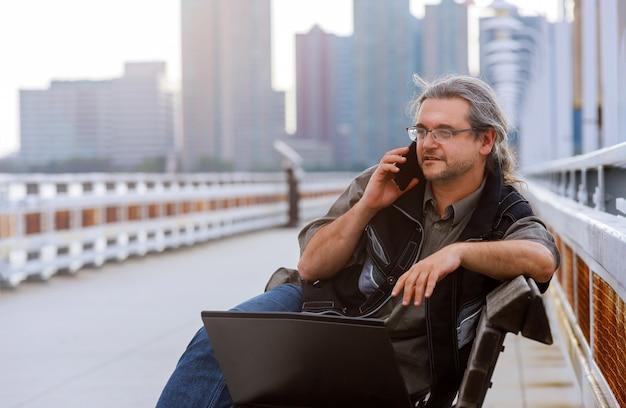 Geschäftsmann, der auf mit new york-stadtbild mit intelligentem telefon in im freien sitzt.