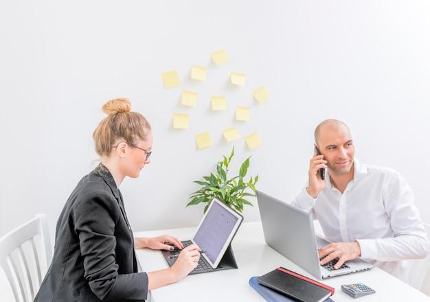 Geschäftsmann, der auf mobiltelefon während sein partner arbeitet an laptop im büro spricht
