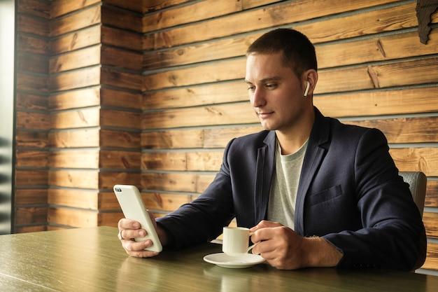 Geschäftsmann, der auf ohrhörern zu seinem mobile hört