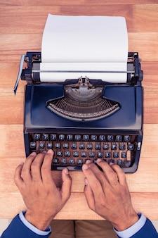 Geschäftsmann, der auf schreibmaschine am hölzernen schreibtisch im büro schreibt