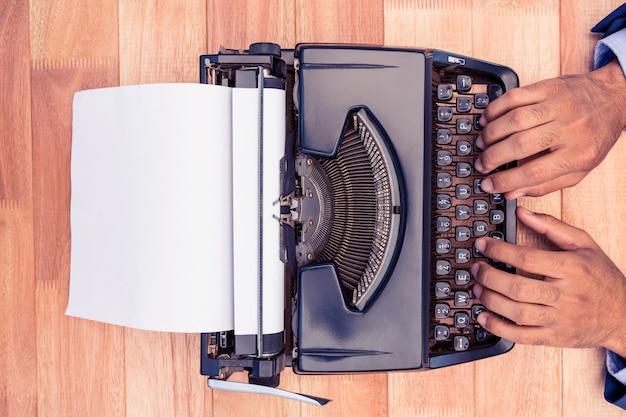 Geschäftsmann, der auf schreibmaschine am schreibtisch im büro schreibt