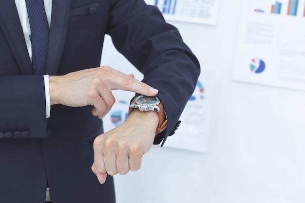 Geschäftsmann, der auf seine armbanduhr schaut.