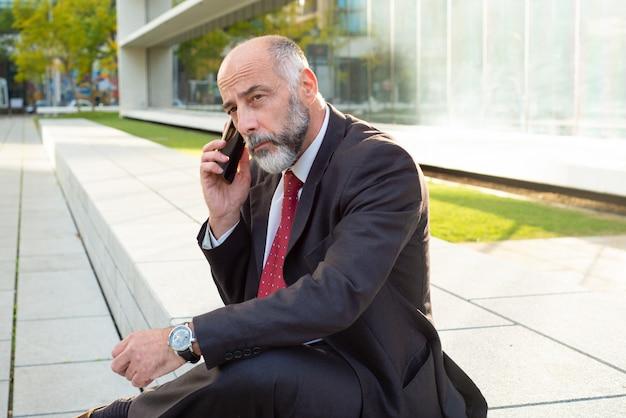 Geschäftsmann, der auf smartphone spricht und beiseite schaut