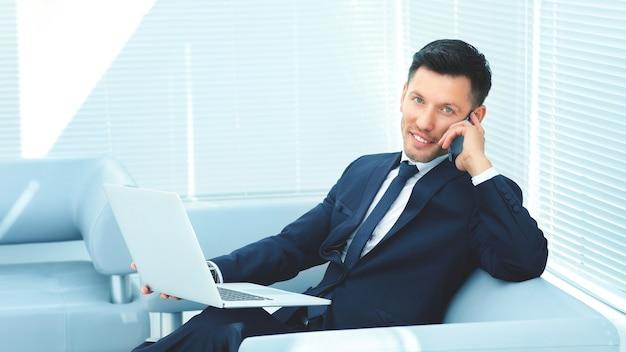 Geschäftsmann, der auf sofa im büro sitzt, einen laptop hält und auf handy spricht