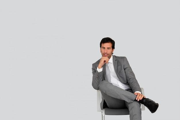 Geschäftsmann, der auf stuhl auf grau sitzt
