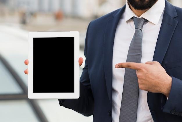 Geschäftsmann, der auf tablette zeigt
