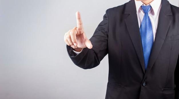 Geschäftsmann, der auf touch screen schnittstelle über grauem hintergrund von hand eindrückt