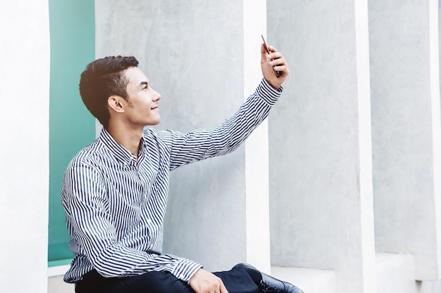 Geschäftsmann, der auf videoanruf oder selfie über smartphone spricht