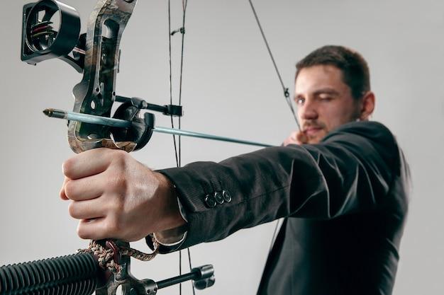 Geschäftsmann, der auf ziel mit pfeil und bogen zielt, lokalisiert auf grauer studiowand