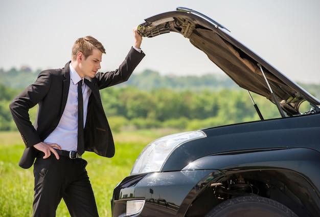 Geschäftsmann, der aufgegliedertes auto überprüft.