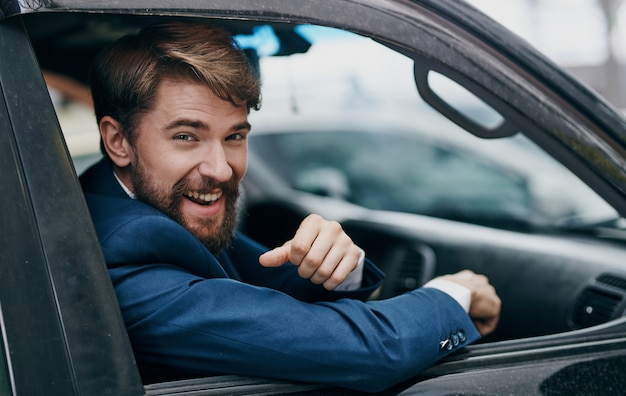 Geschäftsmann, der aus dem autofensterausflugprofi herausschaut. hochwertiges foto