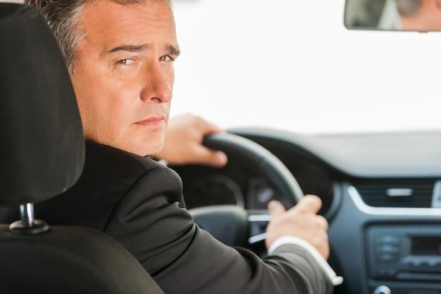 Geschäftsmann, der auto fährt. rückansicht eines selbstbewussten reifen geschäftsmannes, der auto fährt und über die schulter schaut
