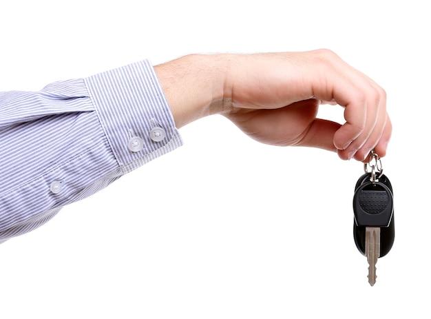 Geschäftsmann, der autoschlüssel lokalisiert auf weiß hält