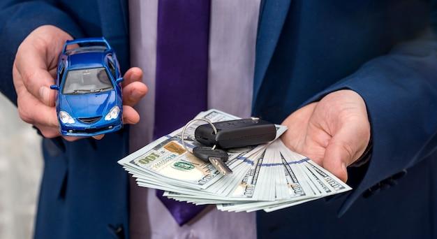 Geschäftsmann, der autoschlüssel, spielzeugauto und geld hält