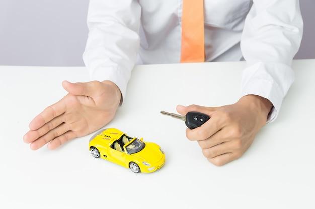 Geschäftsmann, der autoschlüssel und ein miniaturautomodell, ein selbstgeschäft und ein finanzkonzept hält