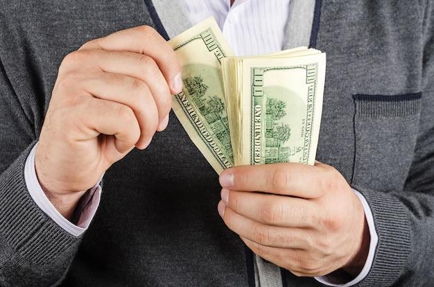 Geschäftsmann, der bargeld-dollar in händen hält. konzept des finanzerfolgs.