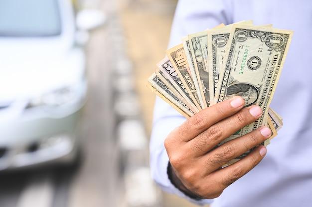 Geschäftsmann, der bargeld in der hand auf autohintergrund hält.