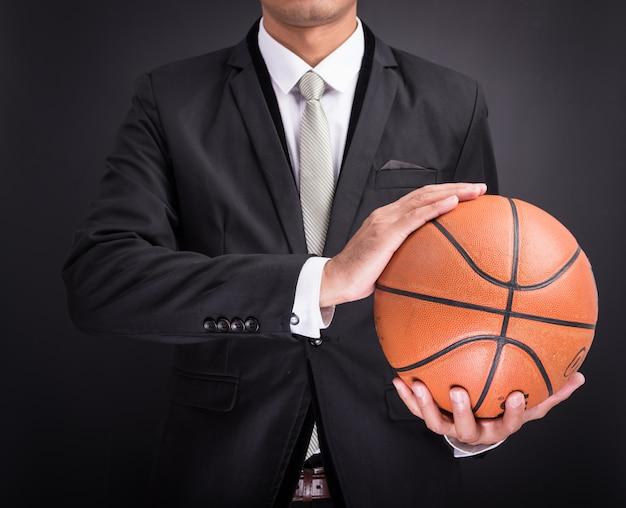 Geschäftsmann, der basketball hält