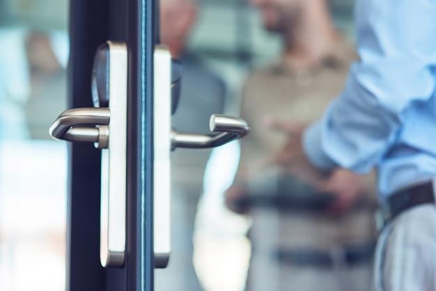 Geschäftsmann, der bei der arbeit beim öffnen der glastür im modernen selektiven fokus des büros eingeht