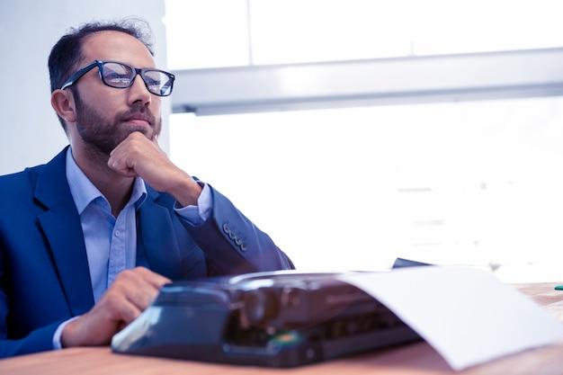 Geschäftsmann, der beim arbeiten an schreibmaschine schreibtisch im kreativen büro weg betrachtet