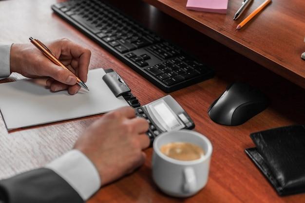 Geschäftsmann, der berechnungen tut, kaffee notiert und trinkt