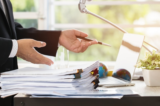 Geschäftsmann, der berichtspapiere mit diagrammen, diagramme auf stapeln von dokumentdateien für finanzierung vorbereitet