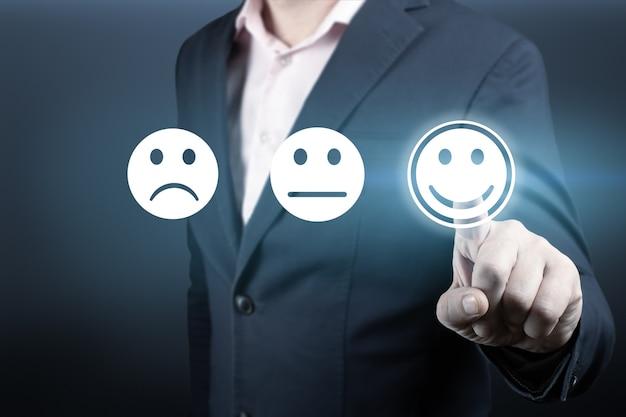 Geschäftsmann, der bewertung mit glücklichem symbol gibt. kundenservice und zufriedenheitskonzept