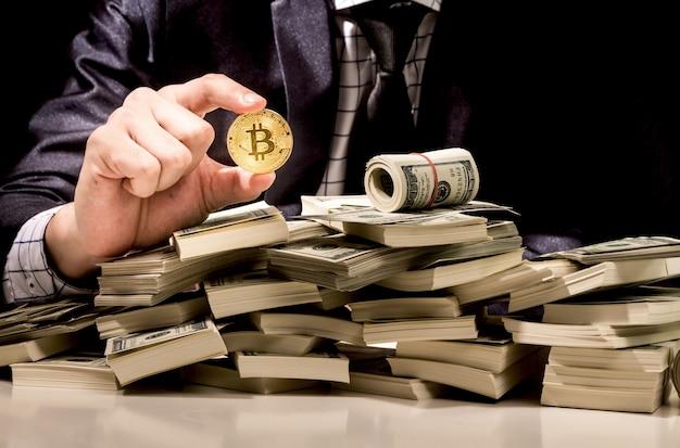 Geschäftsmann, der bitcoin auf schwarzem hintergrund hält